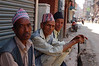 Nepali men in traditional Newari caps enjoying the cool morning