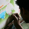 Young Tibetans with good eyesight paint intricate tankhas.