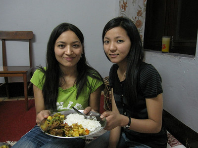 Bhawani and Dalucky hold my dinner plate at Chura's house.