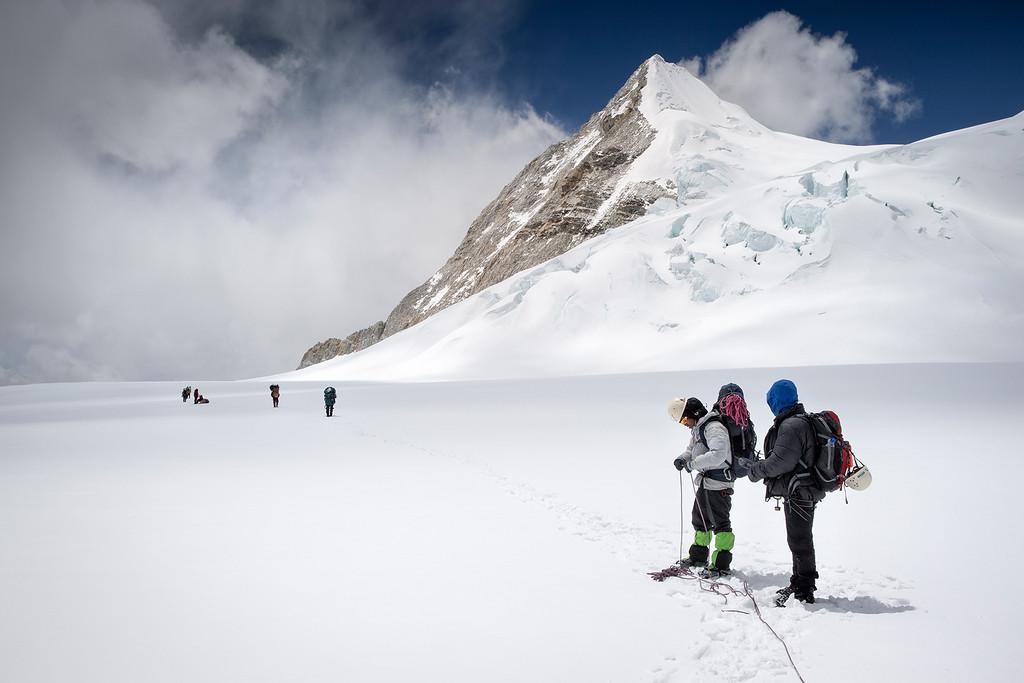 Mounteineer and porters crossing Baruntse Gacier