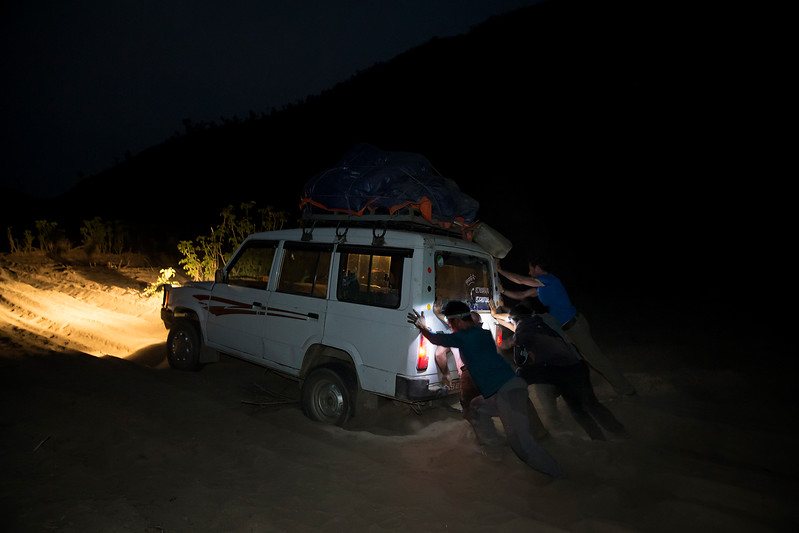 Tourist pushing car stuck in sand