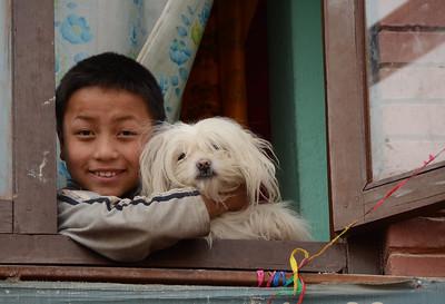 A boy and his dog at Boudhanath (aka Boudha) Tibetan Stupa in Kathmandu, Nepal.