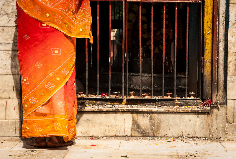 Worshipper wearing an orange sari outside a temple, Kathmandhu, Nepal