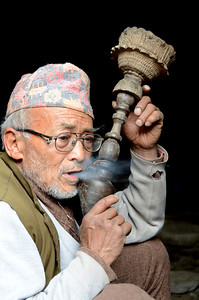 Smoking an antique style pipe in Bhaktapur, Nepal.