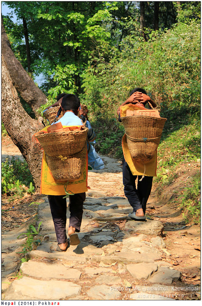Kids carrying hand weaved basket full of bricks