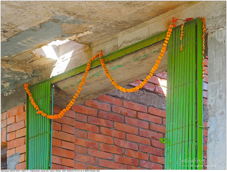 Marigold flower garland tied to the gate frame