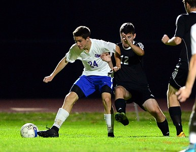 Neshaminy's Chase Rider (#24, left) wards off Truman's Rob Best (12) in boys soccer matchup between the schools Tuesday, Oct. 18 at Harry Franks Stadium, Langhorne, Pa. (John Gleeson – 21st-Century Media)