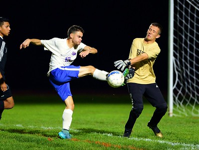 Neshaminy's Nick Lindsey (13, left) pressures Truman goalie Dawson Black.