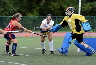 Elayno Curtain (#22) , Olivia Musto (28) and Margaret D'Auria (0) perform hockey duel.