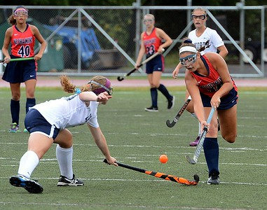 Neshaminy's Emily Alexis (#16) flips ball over CR North junior Bridget Thompson's (30) stick.