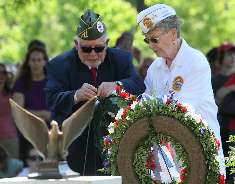AMVETS Commander Gary Grove and Ladies Auxiliary Chaplain Lila McClintock place a wreath near the veterans memorial in New Baltimore. (Photo by Dave Angell)