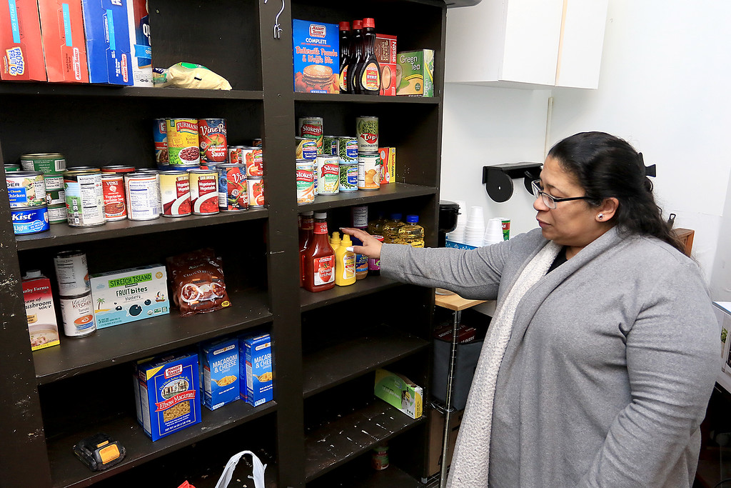 ". New Beginnings Ministry has taken over the shop next door to their church on Main Street in Fitchburg so that they could open up a shop they are calling ""Charity of Love\"" to help those in need.the get donated clothes and sell it for almost nothing to those in the area that need help. Paster Mayra Reyes Lee shows off their new food pantry that they are starting up to go along with all the other stuff they are selling. SENTINEL & ENTERPRISE/JOHN LOVE"