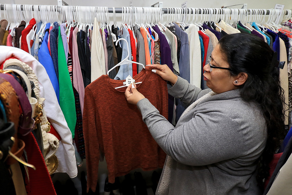". New Beginnings Ministry has taken over the shop next door to their church on Main Street in Fitchburg so that they could open up a shop they are calling ""Charity of Love\"" to help those in need.the get donated clothes and sell it for almost nothing to those in the area that need help. Paster Mayra Reyes Lee shows they price of this shirt to be $1.25. SENTINEL & ENTERPRISE/JOHN LOVE"