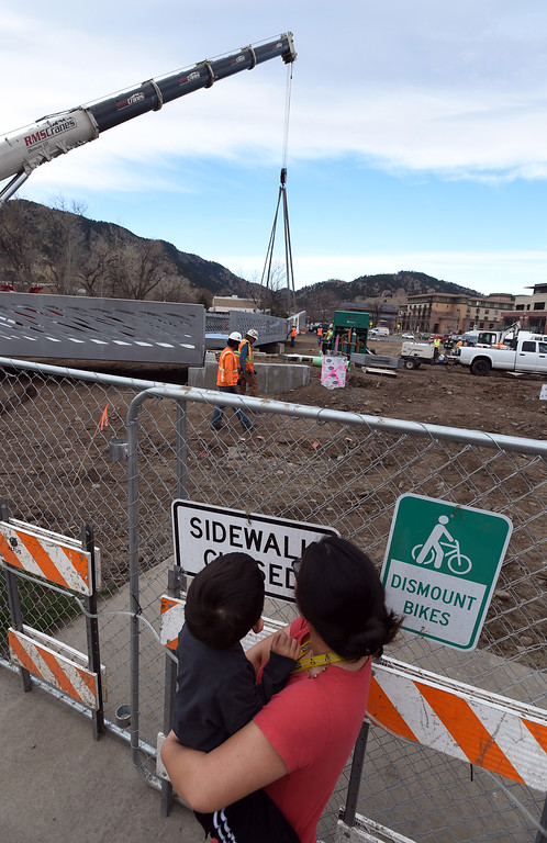 . Laurel Olsen-Horen shows her son, Teddy, 3, the bridge being moved by a crane. The large span of the new Civic Area Bridge in Boulder was set in place on Thursday over Boulder Creek next to the existing bridge that will be removed. For more photos and a video, go to www.dailycamera.com. Cliff Grassmick  Staff Photographer March 16, 2017