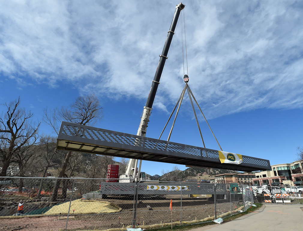 . A giant hydraulic crane moves the bridge into place. The large span of the new Civic Area Bridge in Boulder was set in place on Thursday over Boulder Creek next to the existing bridge that will be removed. For more photos and a video, go to www.dailycamera.com. Cliff Grassmick  Staff Photographer March 16, 2017