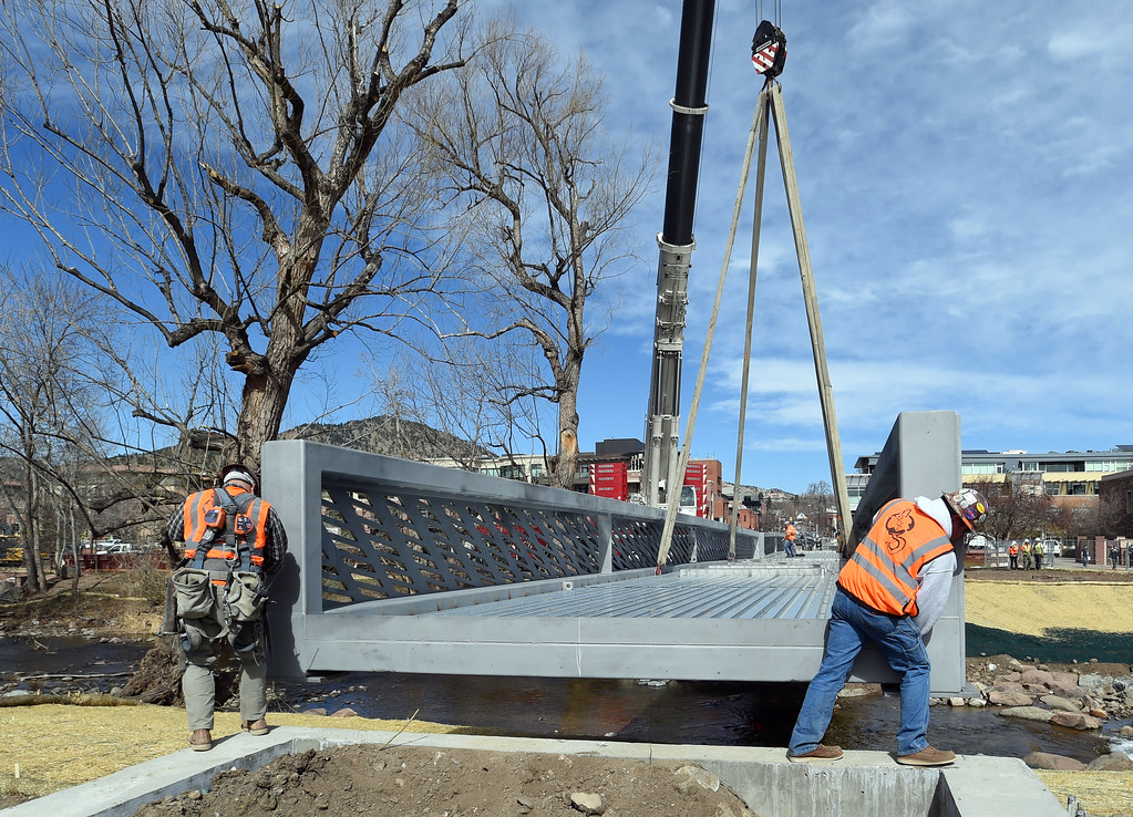 . A giant hydraulic crane moves the bridge into place, while workers  guide the structure. The large span of the new Civic Area Bridge in Boulder was set in place on Thursday over Boulder Creek next to the existing bridge that will be removed. For more photos and a video, go to www.dailycamera.com. Cliff Grassmick  Staff Photographer March 16, 2017