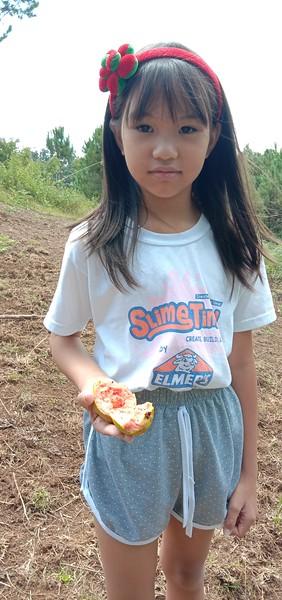 Chin Chin holding a fresh Guava