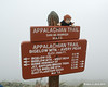 Miles hangs on to the summit sign of Bigelow Mountain, Avery Peak so he doesn't blow away