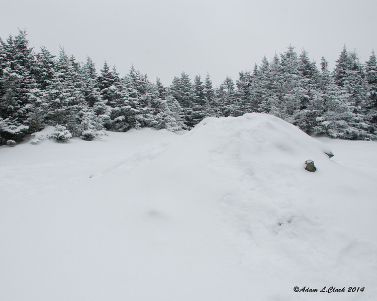The summit cairn is covered in snow