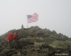 The US flag flying proudly in the clouds at the summit of Mt. Jefferson