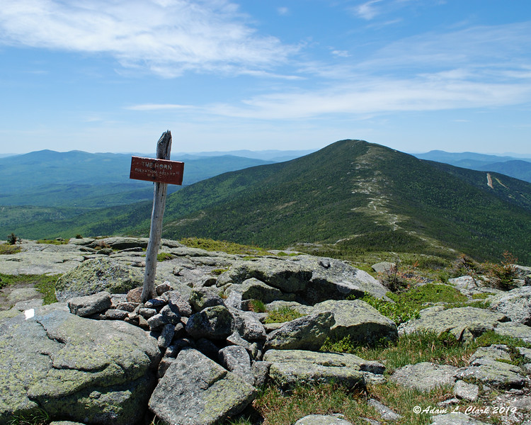 The summit sign and Saddleback Mountain behind