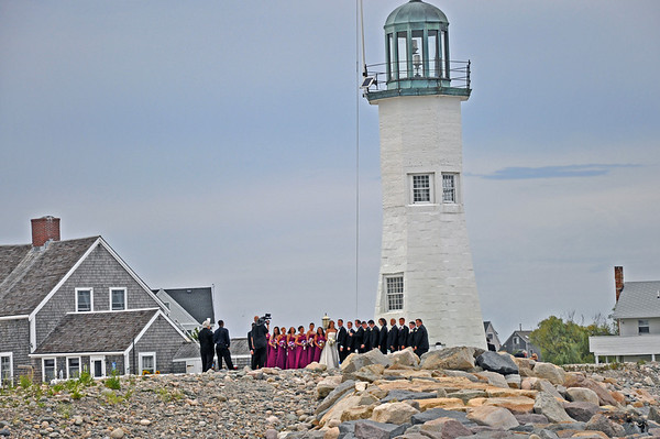 There was a wedding party taking pictures at the lighthouse.