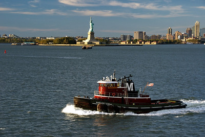 Tugboat Margaret Moran sails by the Statue of Liberty after pulling the Caribbean Princess from the Brooklyn dock