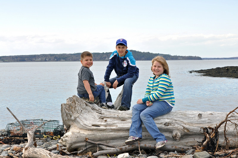 Kathryn, Landry and Jonah on a log on Bar Island.