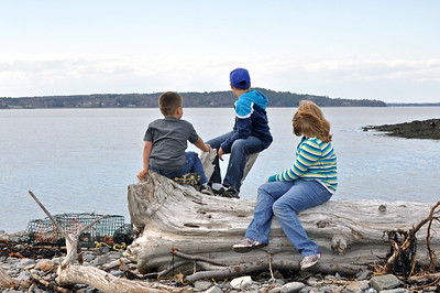 The ocean, lobster trap, the log and the kids make a for pretty nice picture!