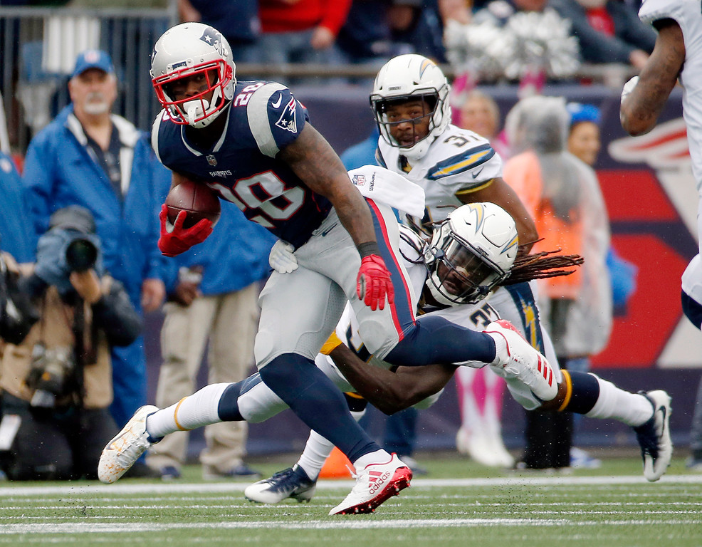 . New England Patriots running back James White (28) runs away from Los Angeles Chargers safety Jahleel Addae (37) during the first half of an NFL football game, Sunday, Oct. 29, 2017, in Foxborough, Mass. (AP Photo/Michael Dwyer)
