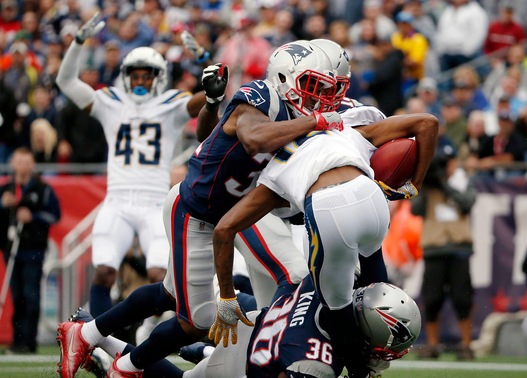 . New England Patriots\' Jonathan Jones top and Brandon King (36) tackle Los Angeles Chargers punt returner Travis Benjamin (12) in the end zone for a safety during the first half of an NFL football game, Sunday, Oct. 29, 2017, in Foxborough, Mass. (AP Photo/Michael Dwyer)