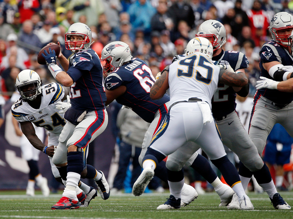 . New England Patriots quarterback Tom Brady (12) passes under pressure from Los Angeles Chargers linebacker Melvin Ingram (54) and defensive end Tenny Palepoi (95) during the first half of an NFL football game, Sunday, Oct. 29, 2017, in Foxborough, Mass. (AP Photo/Michael Dwyer)