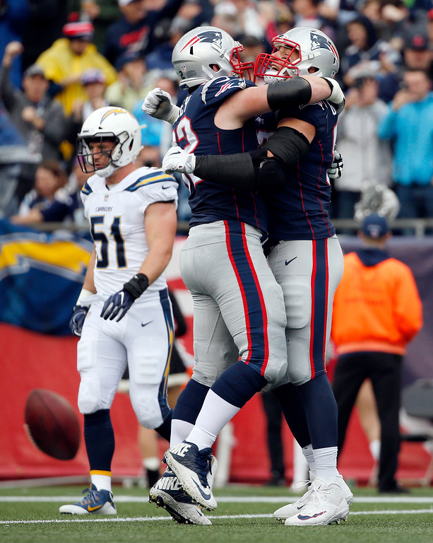 . New England Patriots tight end Rob Gronkowski, right, celebrates his touchdown catch with lineman Joe Thuney during the first half of an NFL football game against the Los Angeles Chargers, Sunday, Oct. 29, 2017, in Foxborough, Mass. (AP Photo/Michael Dwyer)