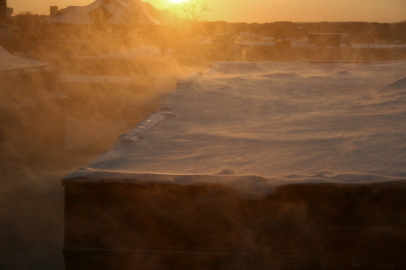 Wind blowing the snow off a roof during sunset