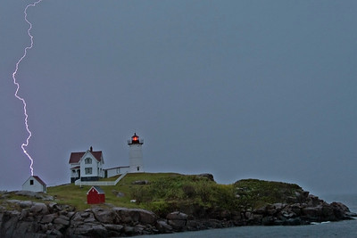 A storm passes by the Nubble Lighthouse, York, Me.  The lightning hit the Atlantic Ocean behind the Island.