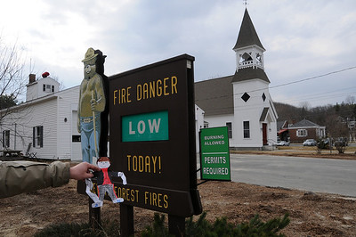 New Hampshire has many churches. The one in the background is typical.  Also, in front of most fire department buildings is a sign that warns the people what the fire danger is. Since everything is wet in the Spring, the danger is low.