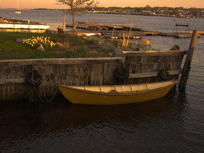 A yellow dory tied to a dock on the Merrimack River, at Newburyport MA.