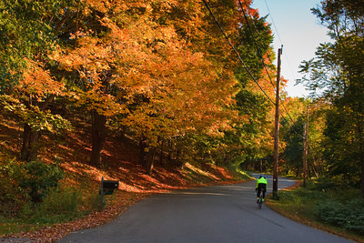 Bicyclist Rides on a Rural Road in Autumn, West Newbury MA