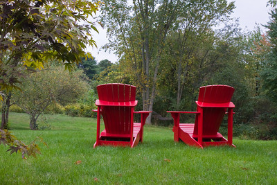 Red Adirondack Lawn Chairs in a Yard
