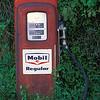 Mobil gas pump growing in woods