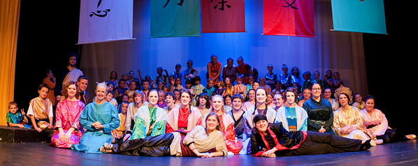 This is the official cast shot. I have much to learn about shooting groups, but I know one thing for now: I'm either pretty lucky or I can produce something under pressure. Not only do I have 145 people here on the stage, including 125 who don't want to sit still, but I have 200 or so behind me in the audience watching me as though this were a bonus portion of the show. Plus it's at least 80 degrees in here, and the sweat may have actually puddled around my feet if it had taken me any longer to get this shot. This was a possibility because my gear (including my ultra-wide lens) is upstairs in the balcony, which is unfortunate because the lens I have down here is not wide enough to capture the entire group all at once. (See photo #229.) Seven get chopped. Not good!  The original plan was to shoot the group shot from the balcony, but those banners hanging down were decapitating people. It didn't help that my camera is mounted on what looked like a toy tripod. So I had a choice: Pretend to faint and hope that someone would drag my body outside, or keep my cool and carefully create a panorama (two images stitched together). Boy did I get lucky that Photoshop was able to handle this. Photoshop told me where the dividing line between the images is, but I can't see it. Yay! Many thanks to this remarkable cast that turned to stone when I needed them to.  This is entirely ambient lighting, spot lights and stage lights, which is much stronger for the folks up front than it is in back. Lighting a group this size with flash is way beyond me right now, so to get even lighting would have meant dimming the front spots and dragging the shutter to brighten the rear. Plus this group has a lot of depth, which demands an aperture closer to f/8 to get everyone into crisp focus. Plus, you really want to avoid as much noise as possible, so it would be better with an ISO of 200.  If we assume that the kids in back are 2 stops underexposed, we're talking a shutter speed of at least 5 seconds. No one could sit perfectly still that long!  I love that I can see Ms. Finley asking the Huns to be quiet!