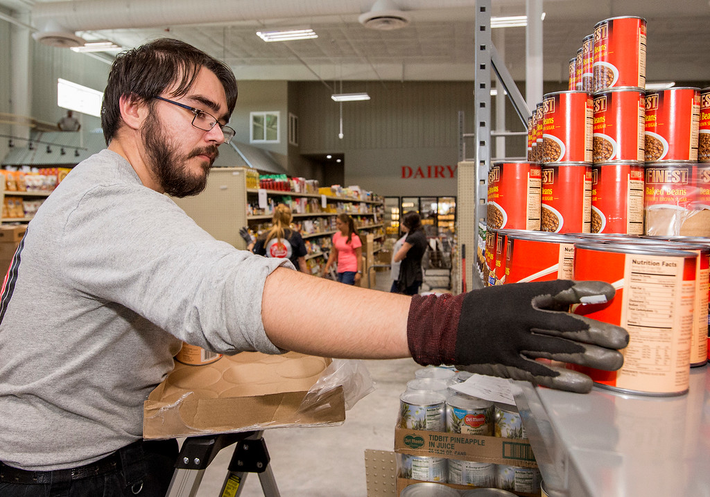 . Esh\'s Grocery Market employee Andy Perez, from Loveland, stocks canned goods on brand-new shelves Wednesday afternoon July 13, 2016 at the company\'s new location at 375 W. 71st St., in north Loveland. (Photo by Michael Brian/Loveland Reporter-Herald)