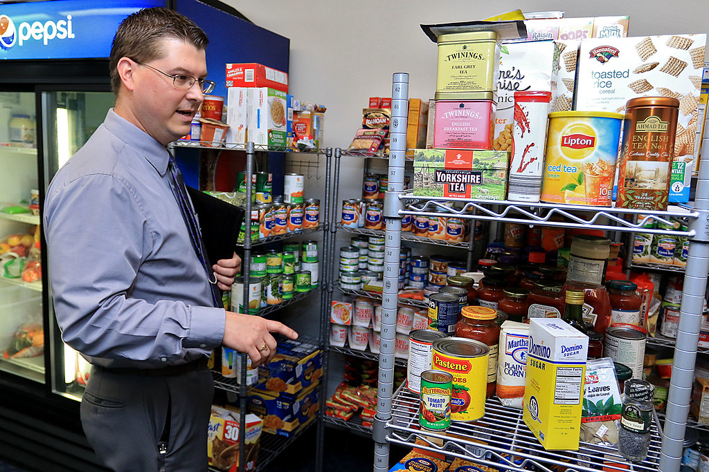 . The new Fitchburg State University Falcon Bazaar food pantry to help students in need held a ribbon cutting on Tuesday, October 16, 2018. FSU Food Service Director Jeff McVoy looks over what they have in the pantry for the students. SENTINEL & ENTERPRISE/JOHN LOVE