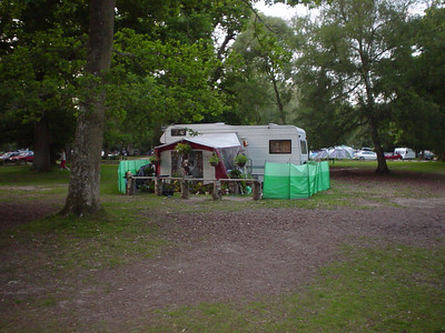 Too Far  Some people take camping just a bit too far.  These people have flower pots and even hanging baskets all around their caravan.  I think they may be working on the site, so it's like home from home.