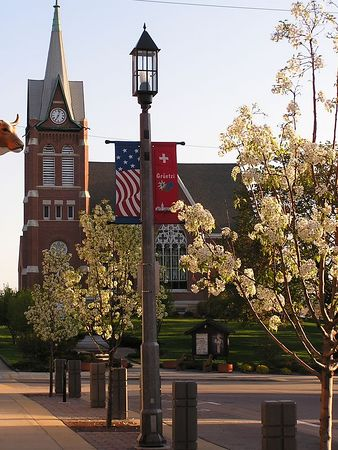 The trees are in bloom, and the flags adorn the lamposts in New Glarus in the spring.
