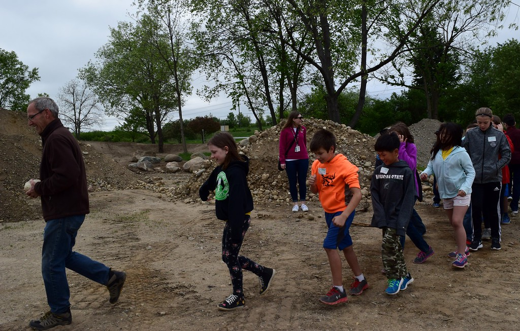 . Fourth graders from Hamlin Elementary school help build a stone path in the learning garden at Innovation Hills in Rochester Hills on Friday, May 19, 2017.