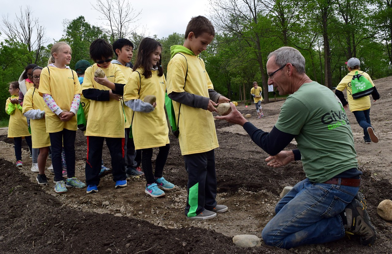 Fourth graders from Hamlin Elementary school help build a stone path in the learning garden at Innovation Hills in Rochester Hills on Friday, May 19, 2017.