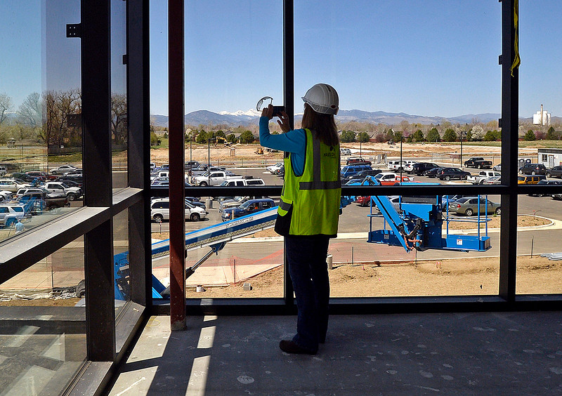 Irene Josey, Larimer County Treasurer, takes a photo of the view from the second floor of the new Larimer County building under construction Friday, April 27, 2018, in Loveland. The Larimer County commissioners and other county employees who work in Loveland and Fort Collins took tours of the new building.   (Photo by Jenny Sparks/Loveland Reporter-Herald)