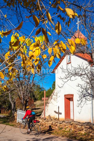 Cyclist passing historic Catholic church in Apache Canyon, NM - D4-C3-0239 - 72 ppi