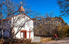Cyclist passing historic Catholic church in Apache Canyon, NM - D4-C3-0244 - 72 ppi